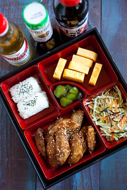 Easy Japanese-flavored chicken wings garnished with sesame seeds and served in a bento box.