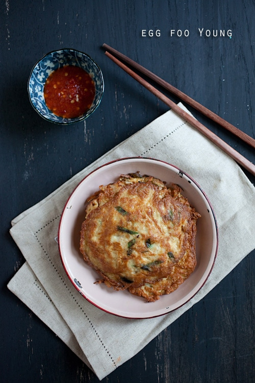 Delicious Chinese omelet, egg foo young, with pork and vegetable filling. Popular egg dish that is placed on a plate with hot sauce on the side.