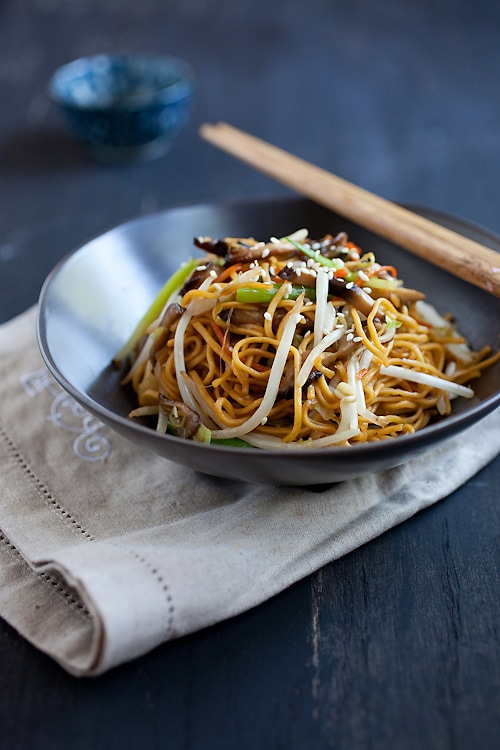 Colorful vegetable chow mein with mushrooms and sprouts in bowl with chopsticks.