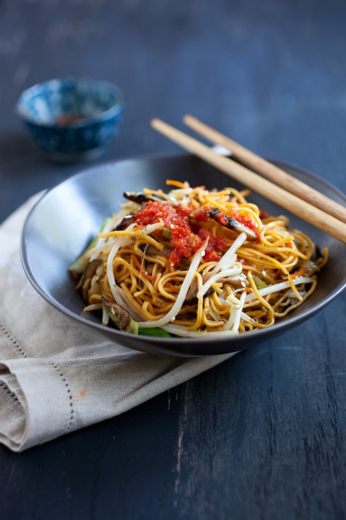 Bowl of Chinese vegetable stir fry noodles with red chili sauce and bean sprouts in bowl with chopsticks.