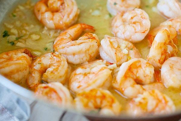 Shrimp in garlicky and buttery shrimp scampi sauce in a skillet.