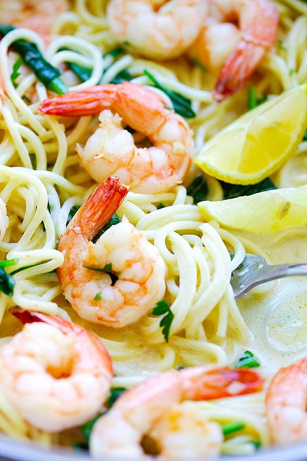 Close up easy shrimp pasta recipe with shrimp, spaghetti in a creamy white sauce and spinach.