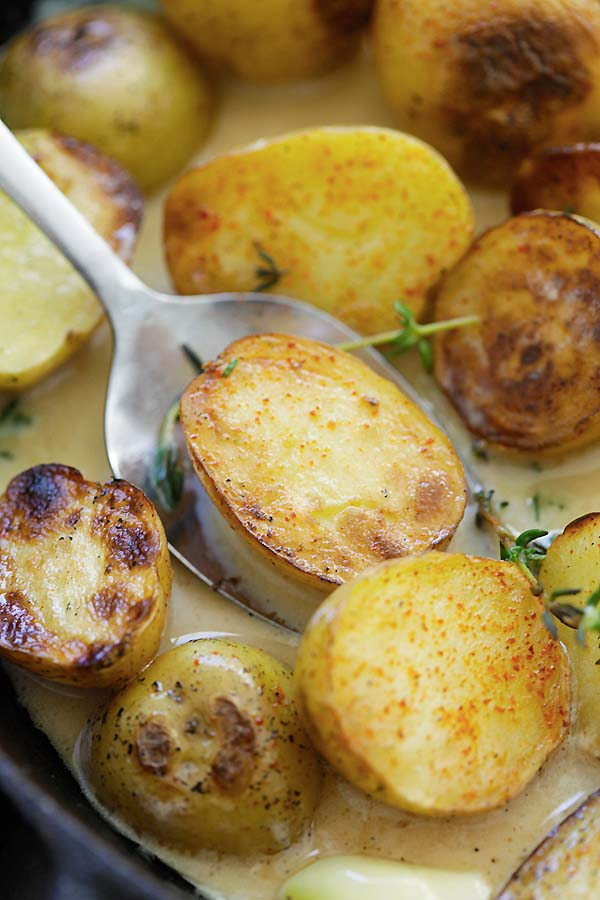Close up white creamy garlic thyme golden potatoes.