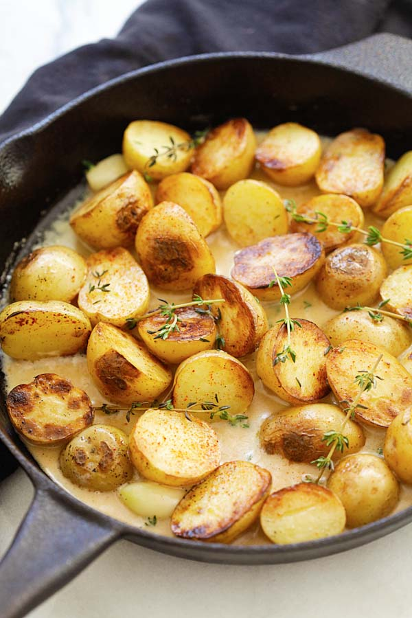 Easy and quick creamy potatoes with garlic thyme in buttery and homemade creamy sauce in a skillet.