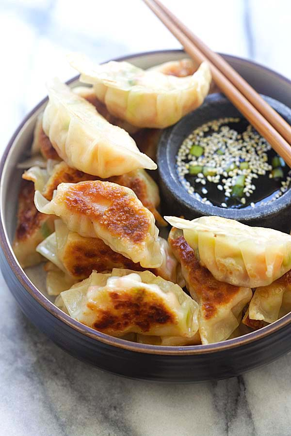 Shrimp gyoza filled with shrimp and cabbage in a serving dish with a side of gyoza dipping sauce.