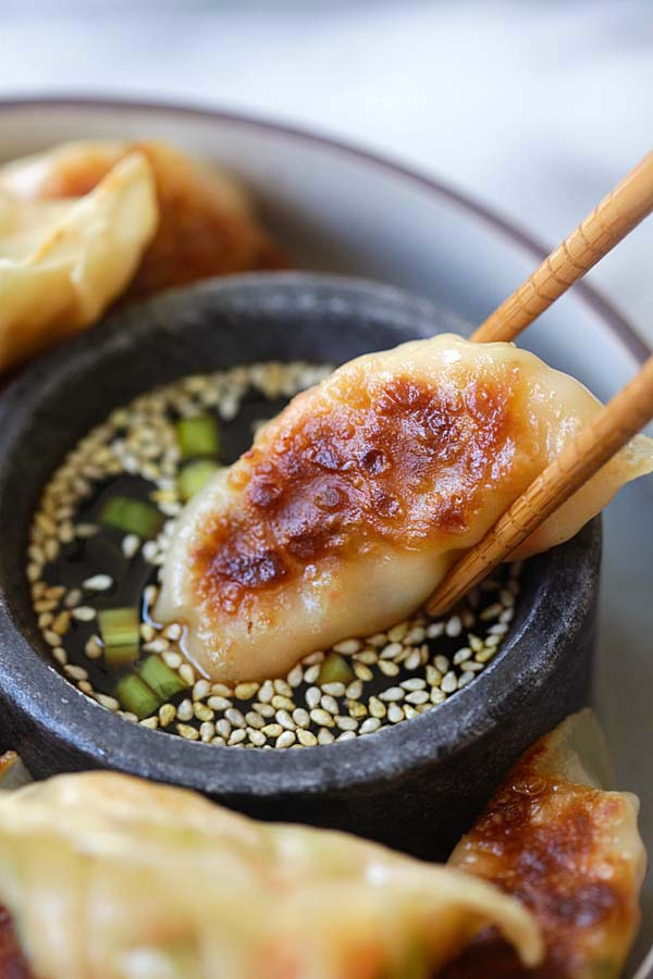 Homemade healthy shrimp gyoza dipped in gyoza dipping sauce with a pair of chopsticks.