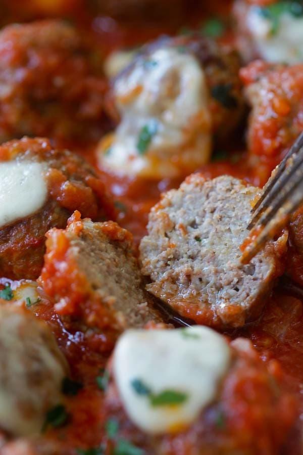 Easy meatball casserole with beef meatballs, one cut in half.