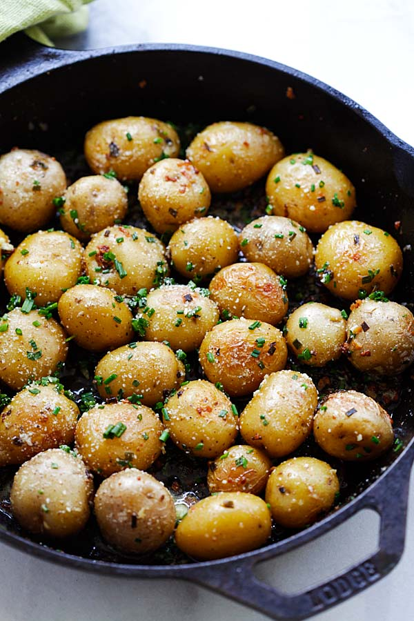 Easy homemade roasted baby potatoes with garlic, chives, butter and Parmesan cheese in a skillet.