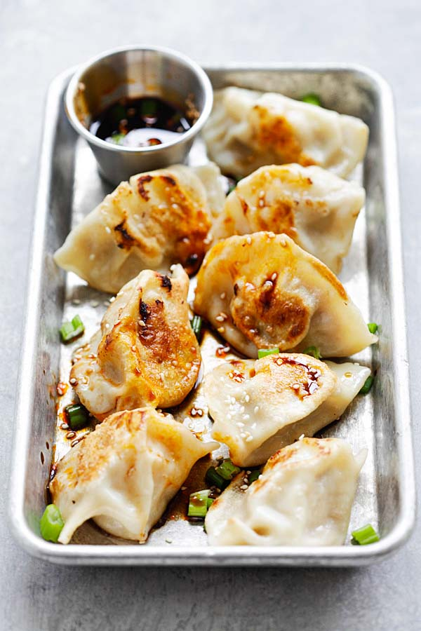 Homemade chicken dumplings with a side of dumpling sauce.