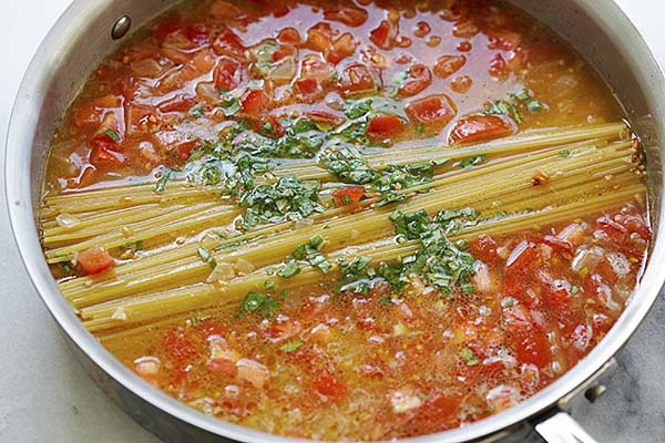 Spaghetti, tomatoes, chicken broth and herb in a pot for one pot pasta.
