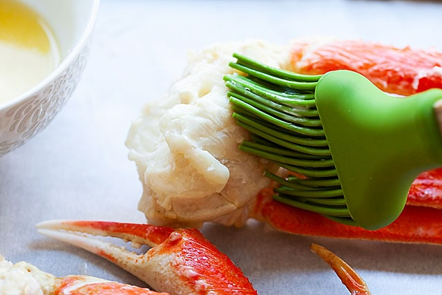 Brushing butter on snow crab.