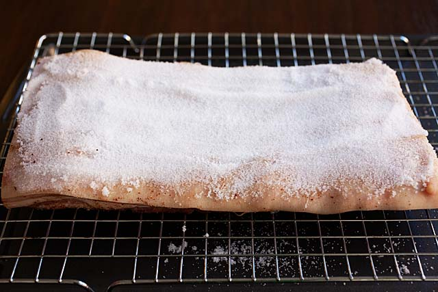 Adding salt to to the skin of pork belly.